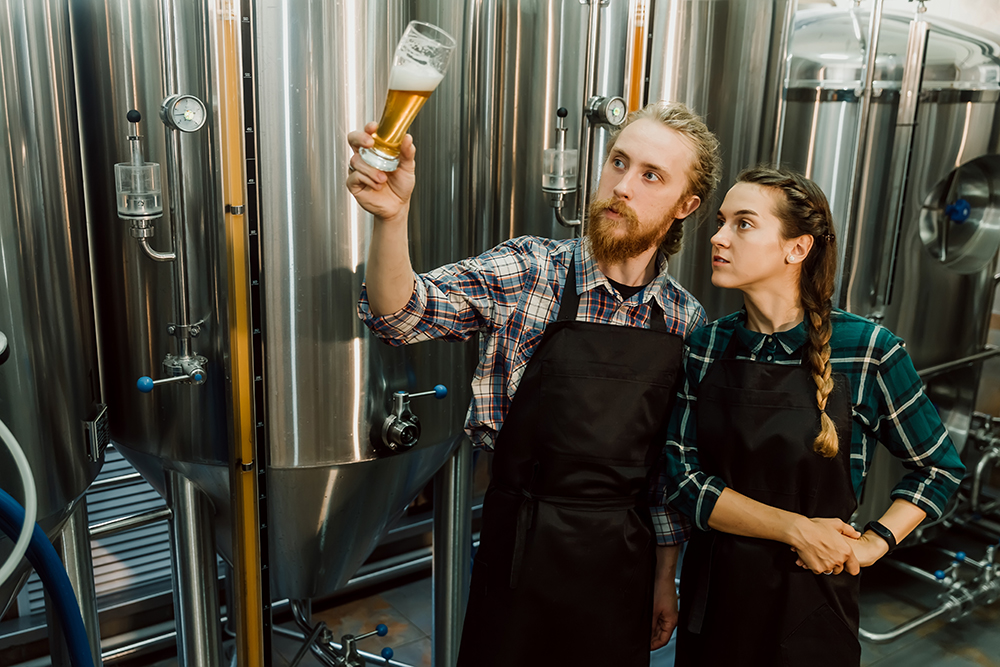 brewers holding up glass of beer by brewing tanks to analyze